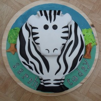Zebra Cake Large sponge with vanilla filling.Small sponge on top for his head.Rolled fondant with black fondant gently rolled into the white with a...