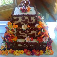 First Wedding Cake The bride wanted fall colors and wild flowers. The cake is marble with ivory buttercream icing and chocolate icing scroll work. The couple...