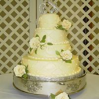 Buttercream Wedding Cake With Gumpaste Roses This is a 4 layer ivory buttercream wedding cake. 2 layers had a quilting design while the other 2 layers had a scrollwork design. The cake...