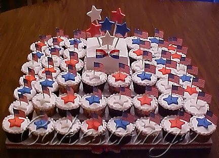 "4Th Of July Cupcake Tiers 6"" square middle cake with fondant stars on cookie sticks and bow, surrounded by alternating white and chocolate cupcakes iced and..."