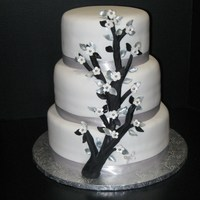 Branch Wedding Cake  Branch wedding cake8-10-12 inch tiered cake with black branch, silver & black leaves, white five pedel flowers with silver dragees in...