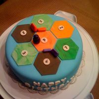 Settlers Of Catan Game 9 inch blue fondant cake with marbled fondant game pieces on top. Inspired by the game board for the game Settlers of Catan.