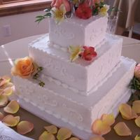 Autumn Blossoms This square, ivory wedding cake is adorned with a variety of fresh floral blossoms in shades of orange, peach, and pink. The couple chose a...