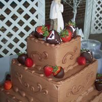 Happily Ever Chocolate This chocolate groom's cake is embellished with chocolate covered strawberries, some of which are dipped to resemble tuxedos. The...