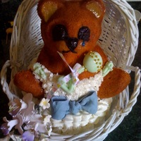 Bear In Basket all edible except basket; bear sits on top of oval cake; rattle and bow fondant; flowers gumpaste