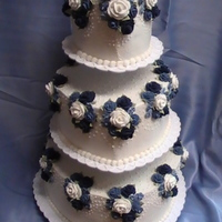 Blue & White Rose Wedding Cake This heart shaped cake is covered in butter cream icing. The flowers are royal icing roses and apple blossoms