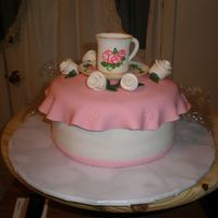 Tea Cup Cake White WASC filled & iced w/BC & covered w/SI. Tea cup, saucer & flowers made from gumpaste. Tea cup & saucer are hand-...