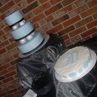 Happy 50Th Birthday  This cake was made for a 50th Birthday celebration. The stacked cake is vanilla with buttercream and a fondant overlay. The second cake is...