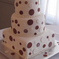 "Polka Dot Cake 10"" square with 8"" and 6"" rounds covered in fondant. Polka dots are cinnamon-colored and white fondant. Border is made with..."