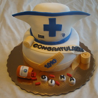 Nurses Hat Graduation carved 6 inch top tier gum paste for front of hat, fondant covered, edible images of school logos.