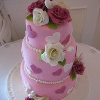 Hearts And Flowers Wedding Cake Three tiered round wedding cake with gumpaste roses and doodads? I am not sue what else to call the little additions to the cake. The bride...