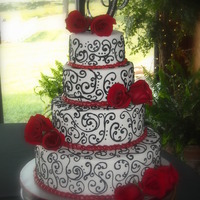 Taylor 4 tier white cake with buttercream icing covered in fondant. Scrollwork is done in royal icing. Fresh red roses. TYFL.