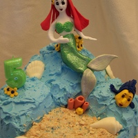 Ariel Mermaid Under The Sea Cake Lemon cake with blackberry pastry cream filling, IMBC frosting. Ariel is gumpaste and fondant. Shells are chocolate. Sand is crushed...