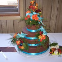 308.jpg Chocolate Buttercream with ribbons and fresh flowers. I love the contrast of the brown, blue, and orange in the flowers