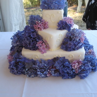 Square Wedding Cake With Hydrangeas Bottom tier chocolate cake with vanilla buttercream filling. Top two tiers white cake with raspberry filling. MMF with piped swirls and...