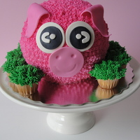 Oink Oink Piggie Piggie cake made with butter cream icing and fondant accents. Mini cupcakes to join and make a grass like accent... Enjoy!