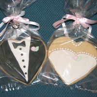 Bride & Groom Coookies heart shape sugar cookies w/Antonia74 icing and fondant flower/leaf. Next time I will use smaller heart cookie cutter and photographe...
