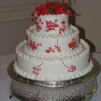 "Red & White Wedding Cake   14"" 10"" 6"" round BC with gumpaste flowers & red BC on side of cake to mimic the bride's wedding dress."