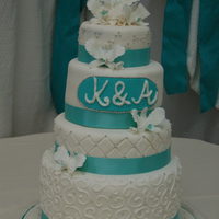 White & Aqua Alternate layers of chocolate and vanilla cake with vanilla buttercream. Handmade gumpaste lilies.