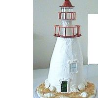 Lighthouse  First attempt at doing a lighthouse. It is made with 5 layers of cake and BC, shells are made of chocolate, sand is graham crackers and top...