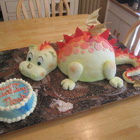 "Dragon & Smash Cake Dragon cake for my great nephew's first birthday. The body is carved from 6"" high stack of 12"" round cakes. Head is carved..."