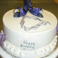 Purple Pumps Vanilla cake with gum paste pumps, charm bracelet and butterflies.