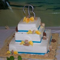 Beach Themed  Chocolate and vanilla cake covered in buttercream and ribbon. The seashells are candymelts, the sand dollars are fondant, and the calla...