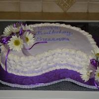 Birthday Girl At The Bank Paisley shape white cake, buttercream icing, fresh flowers and ribbon.