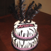 Arcenia's Zebra White Chocolate cake with Vanilla Mousse filling. Iced in Buttercream and deccorated with fondant accents.