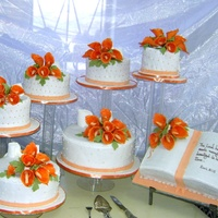 Orange Theme Wedding Cake   A seven tired wedding cake;six round and one Bible,all with tiger lilies on top.