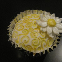 Daisy Cupcake Cupcake covered with fondant and decorated with fondant daisy and luster dust.