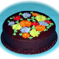 Fall Colors A white cake with raspberry filling, covered with chocolate fudge buttercream icing. Flowers are made from buttercream. Thanks for looking...