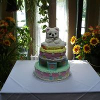 Teddy Bear Baby Shower Cake  This is a two tier baby shower cake with the second tier sitting on gum paste blocks. The top tier has a decorated teddy bear cake on top...