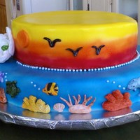 Sea And Sky Luau cake for a party at my son's school. air brushed over fondant, with hand made fondant Gardenia's.