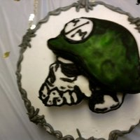 Metal Mulisha round cake with 3d carved skull on top, hand painted on fondant
