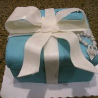 Tiffany Cake wasc cake with strawberry fiiling covered in bc. fondant is white choc fondant. the ribbon is half gp half fondant. the bow is dusted with...