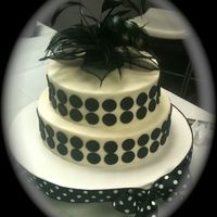 Polka Dots BC icing with black satin ice fondant dots. The topper was a corsage of mine that I used flower wire to make a stem and stuck in a straw. I...