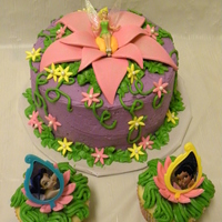 Tinkerbell Cake And Matching Cupcakes  I was asked to match a theme of Tinkerbell with purple green and pink on the main cake and matching cupcakes with a flower to set rings in...