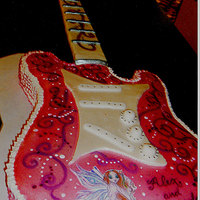 Guitar Cake This cake was shaped into a Guitar , iced in buttercream . Then the top was covered in fondant, painted and decorated.