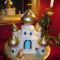 Aladdin Multi-tier cake covered in fondant with gumpaste decorations. Towers made of stacked cookies held together with royal icing. Tops of towers...