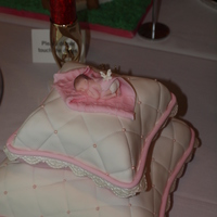 Tiny Miracle Pillow shaped cake layers covered in pink and white fondant accented with fondant lace and rope border. Topped with fondant baby resting on...