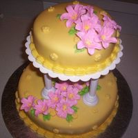 Picture_010.jpg My first tiered cake. Yellow cake with pinneapple filling, covered with yellow fondant. Lily flowers are in RI.
