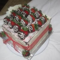 Strawberry Dream 16 chocolate cake w/ strawberry chantilly cremewhite chocolate side panels and topped w/ dipped organic strawberries and drizzled w/ white...
