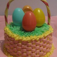 Easter Basket Cake Buttercream basketweave, green coconut for the grass, plastic Easter eggs, and non-edible handle.