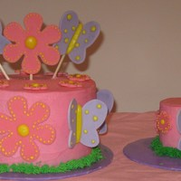Pink Butterfly And Flower Cake Done in pink buttercream with gumpaste flowers and butterflies. For 1 year old's birthday.