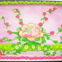 A Budding Baby Shower sheet cake frosted in buttercream and airbrushed with a touch of purple. Green leaves and vines tipped on with accenting flowers to...