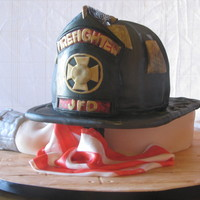 "Fire Fighter Helmet On Coiled Hose This cake was a surprise for a groom who is a fire fighter. It was to resemble the grooms actual helmet. It was on a ""coiled""..."