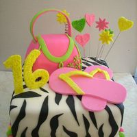 "Sweet Sixteen Square Cake covered in MMF and covered with Zebra stripes out of black fondant. Purse was cut out of two 6"" cakes and covered with..."