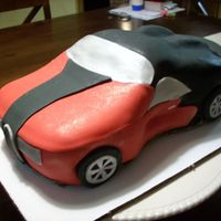 Sports Car Car was carved and covered in fondant. I applied a gold luster dust to give the fondant a little sheen. Next time will apply steam to...