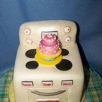 Stove Or Oven White cake sculpted to look like child's oven with fondant birthday cake on top. Oven window was made by melting LifeSavers.